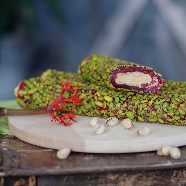 Lazdynų riešutų kremu pripildytas GRANATŲ skonio lukumas padengtas pistacijomis (200 gr.)